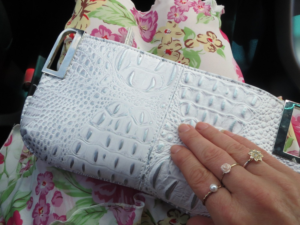 White clutch, floral skirt, rings